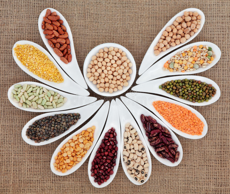 Dried Pulses. Selection in white porcelain dishes over hessian background