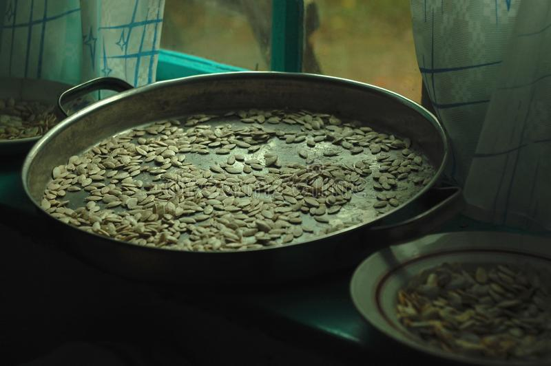 Dried pumpkin seeds in a round metal pan on a wooden rural window sill. Selective soft focus. Dried pumpkin seeds in a round metal pan on a wooden rural window royalty free stock images