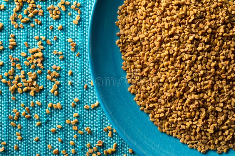 Dried, raw fenugreek seed in blue plate on blue mat background top view flat lay from above. With selective focus stock image