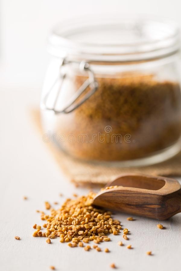 Dried, raw fenugreek seed in storage glass jar on white wooden table background with wodden scoop. With selective focus stock photos