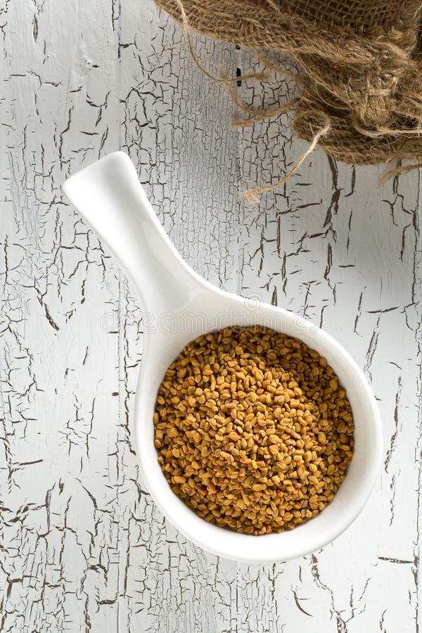Dried, raw fenugreek seed in white bowl on white rustic wooden table background top view flat lay from above. With selective focus royalty free stock images