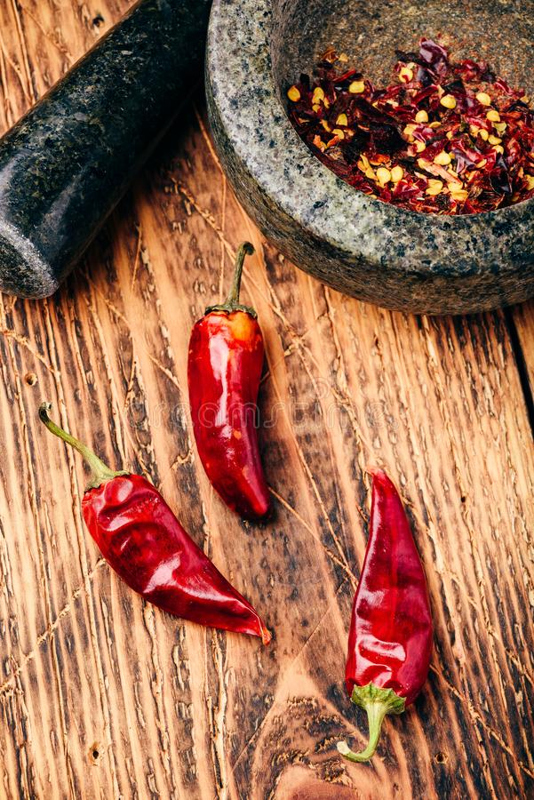 Dried red chili peppers on wooden surface with mortar and pestle royalty free stock images