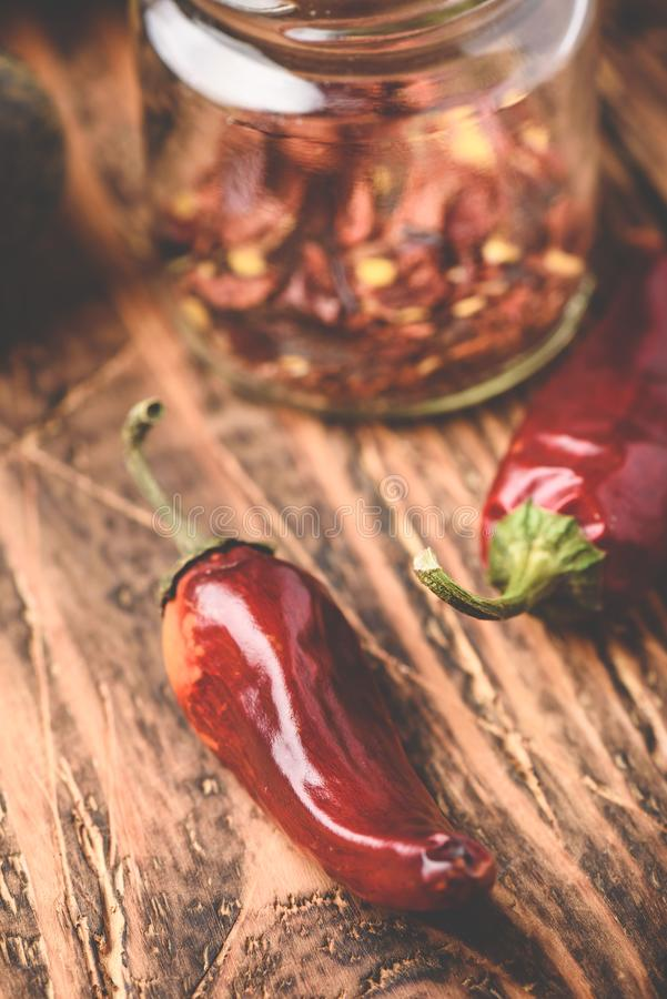 Dried red chili peppers on wooden surface stock image