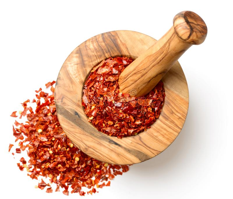 Dried red chilli flakes in the wooden mortar, isolated on white, top view stock images