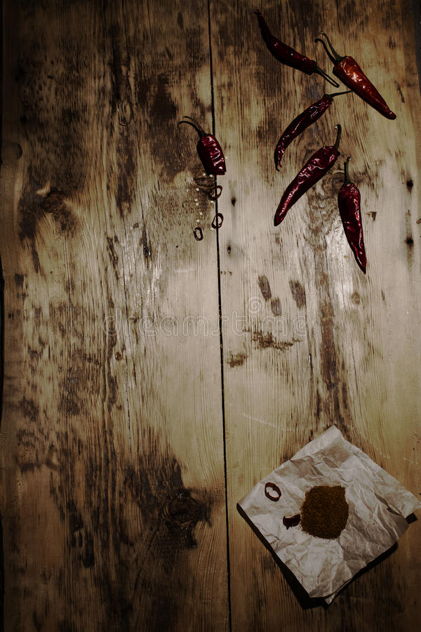 Dried red chilli and ground pepper on a wooden background. Tinted darkened photo stock image