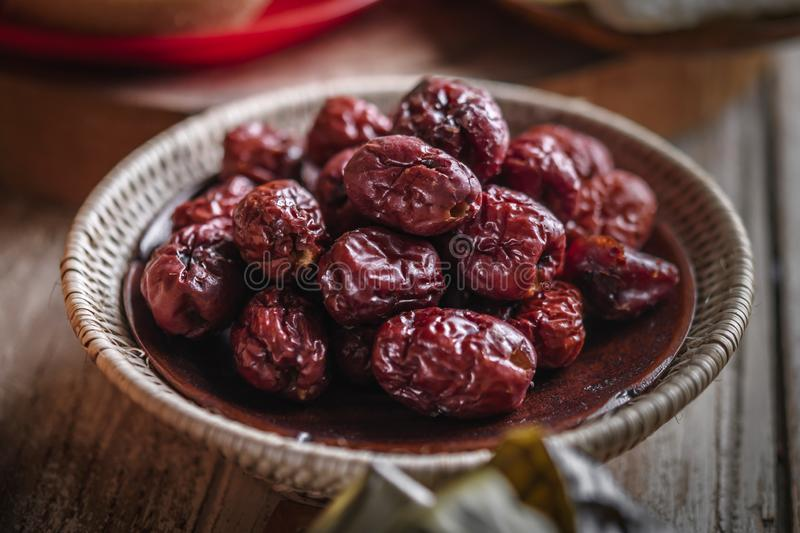 Dried red date or Chinese jujube. Traditional herbal medicine spill. On wooden agriculture asian autumn background basket big china crop dates delicious desert royalty free stock images