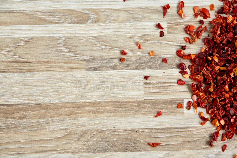 Dried red hot chilly flakes on light wooden background, top view, close-up, macro, shallow depth of field. stock images