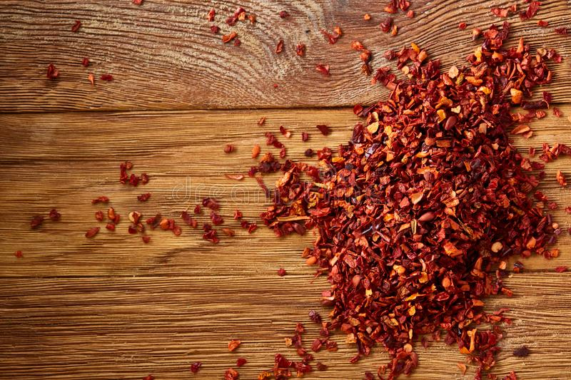 Dried red hot chilly flakes on rustic wooden background, top view, close-up, macro, selective focus. stock photos