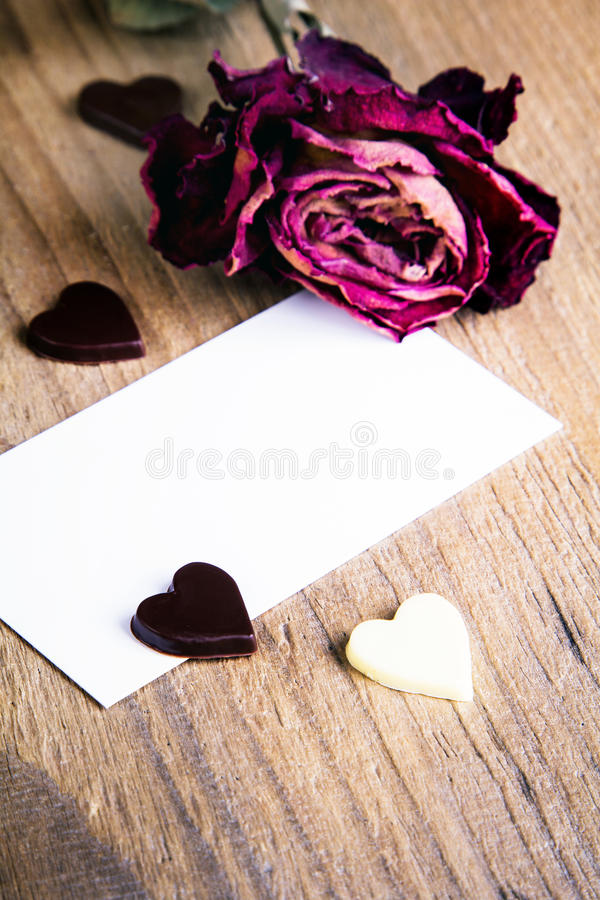 Dried rose, blank business card and chocolate hearts. Copy space stock photography