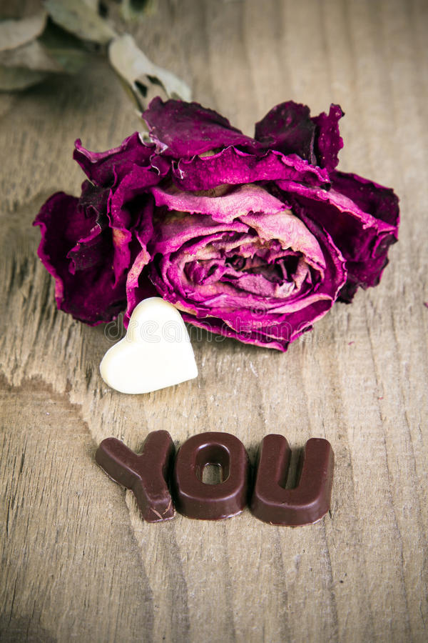 Dried rose and chocolate word YOU. On wooden background royalty free stock photos