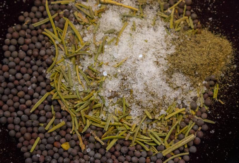 Dried rosemary with black mustard seeds, salt and black pepper powder closeup. Aroma herbs and spices top view. stock photo