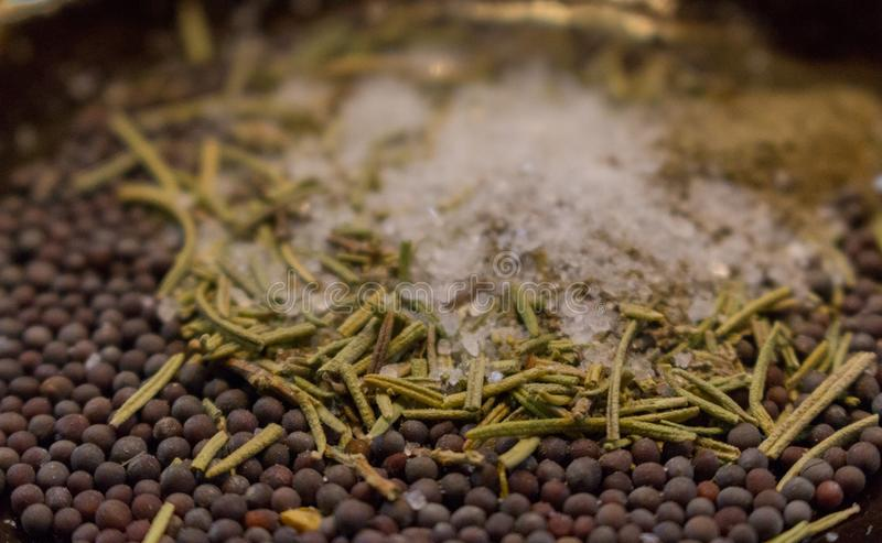 Dried rosemary with black mustard seeds, salt and black pepper powder closeup. Aroma herbs and spices on plate. royalty free stock photos