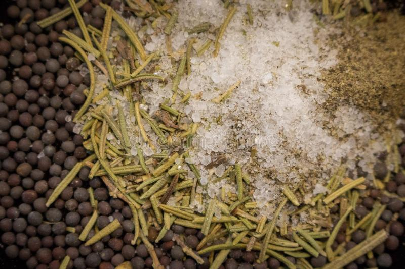 Dried rosemary with black mustard seeds, salt and black pepper powder closeup. Aroma herbs and spices top view. royalty free stock photo