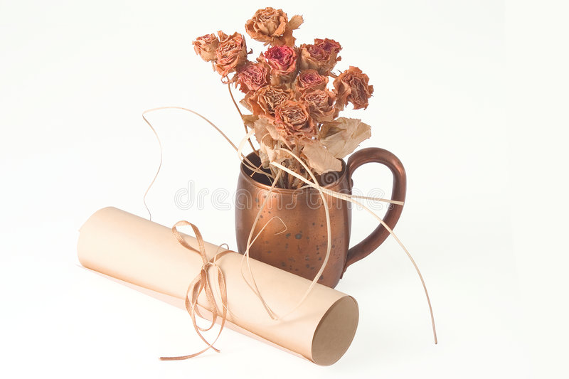 Dried roses in metal cup and scroll royalty free stock photos