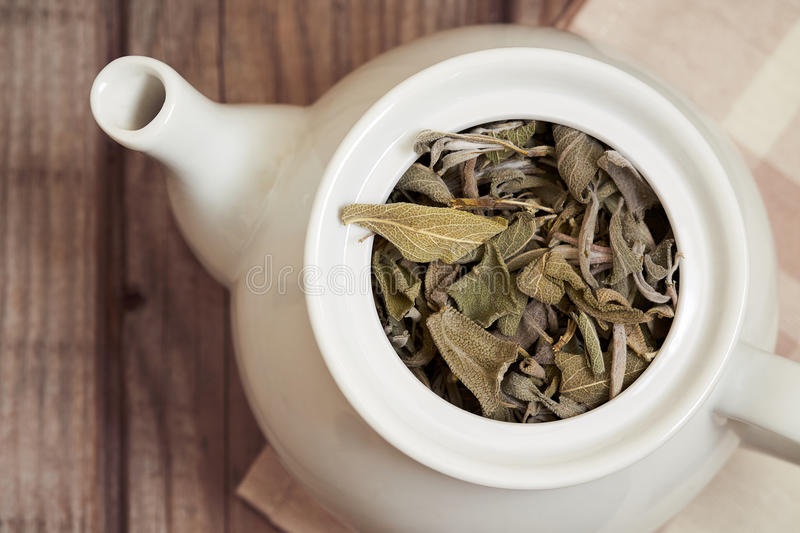 Dried sage leaves. In white teapot on rustic wooden background. Top view royalty free stock photos