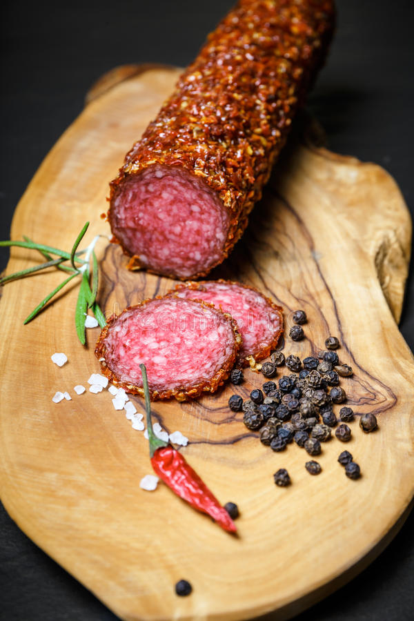 Dried salami crusted in ground red pepper. On dark background stock image