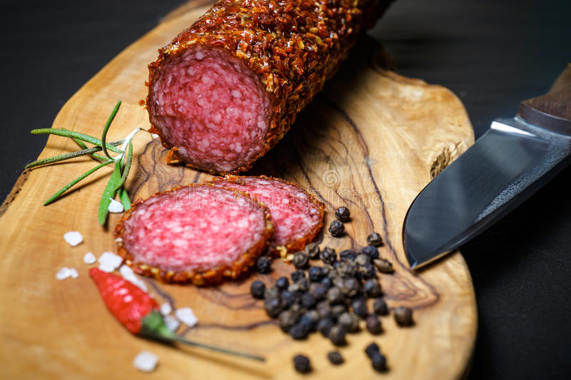 Dried salami crusted in ground red pepper. On dark background royalty free stock photos