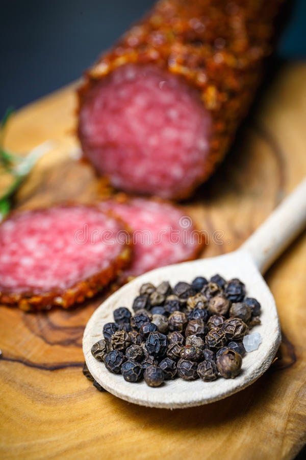 Dried salami crusted in ground red pepper. On dark background royalty free stock images