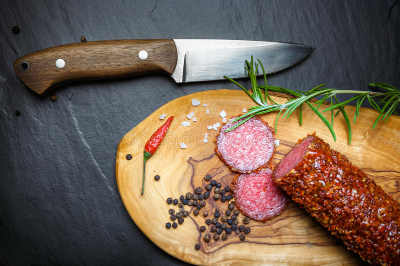 Dried salami crusted in ground red pepper. On dark background stock images