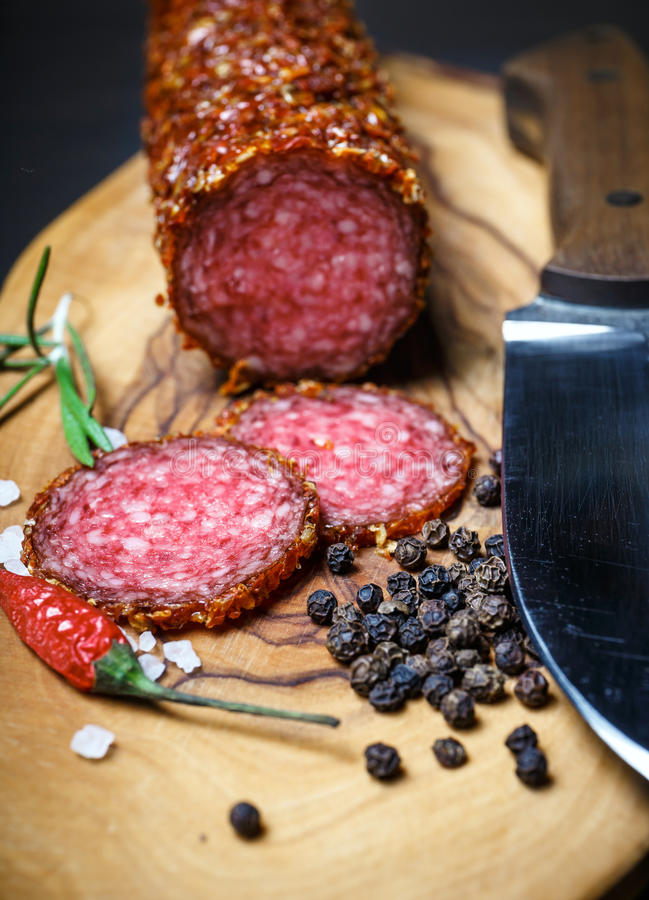 Dried salami crusted in ground red pepper. On dark background royalty free stock image
