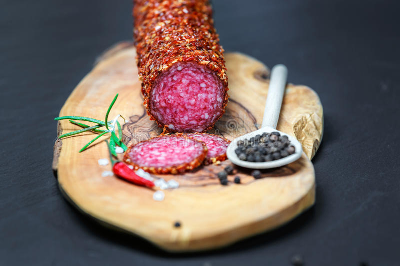 Dried salami crusted in ground red pepper. On dark background stock photography