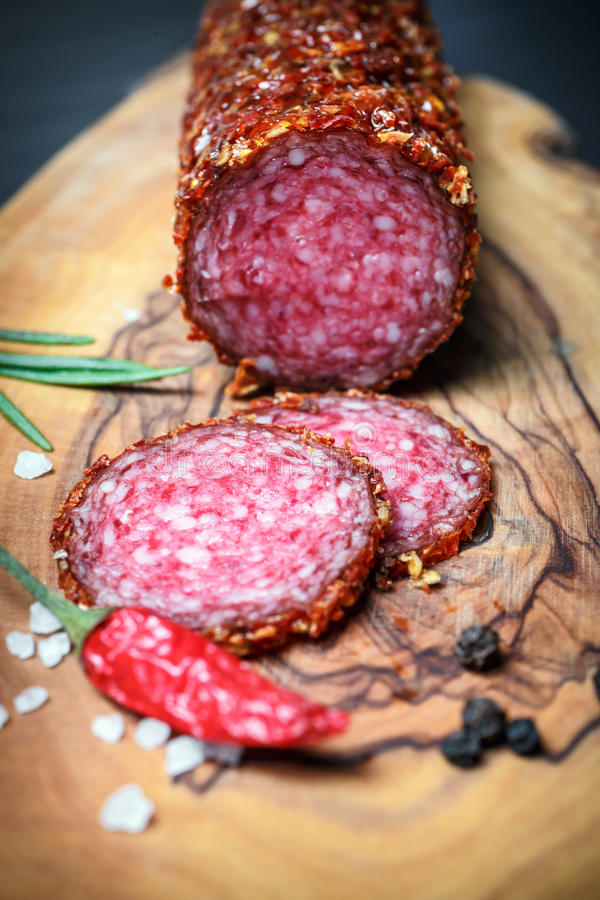 Dried salami crusted in ground red pepper. On dark background stock photos