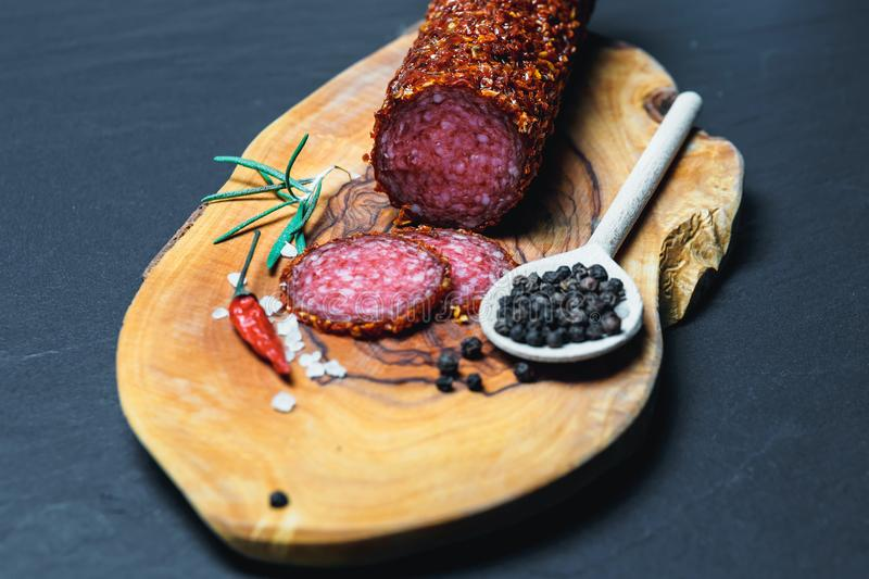 Dried salami crusted in ground red pepper. On dark background stock photo