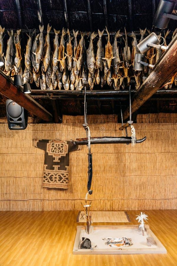 Dried salmons and fireplace inside house of Shiraoi Ainu Village Museum in Hokkaido, Japan royalty free stock image