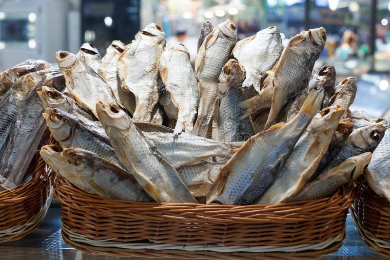 Dried salted perch fish in basket close up, dry sea bass sale on seafood market, tasty stockfish, jerky grouper, salty sunfish. Dried salted perch fish in basket stock photos