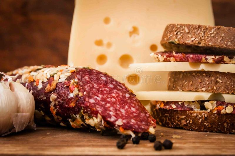 Dried sausage and cheese with holes for breakfast royalty free stock images