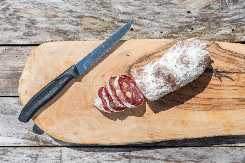 Dried sausage with nuts cut in slices and a knife royalty free stock photos