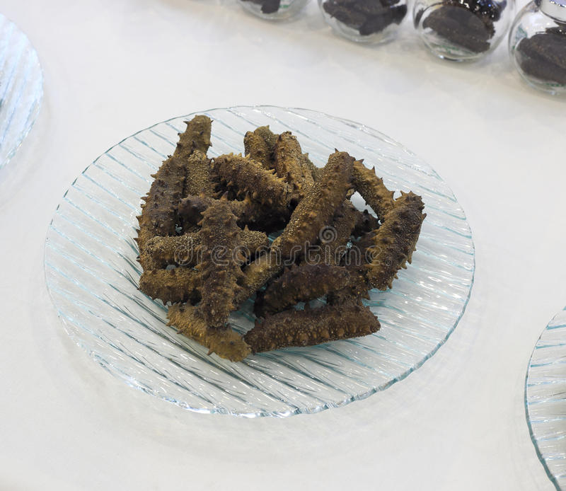 Dried sea cucumber. On the glass plate royalty free stock photo