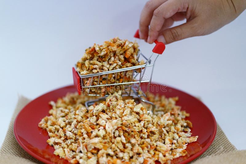 Dried shrimp on shopping carts  There is a man& x27;s hand holding the car  About online dried seafood trading business. Dried shrimp shopping carts there mans royalty free stock images