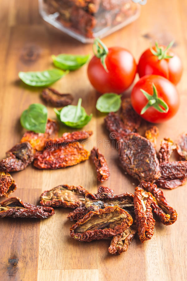 Dried sliced tomatoes and fresh tomatoes with basil leaves. royalty free stock images