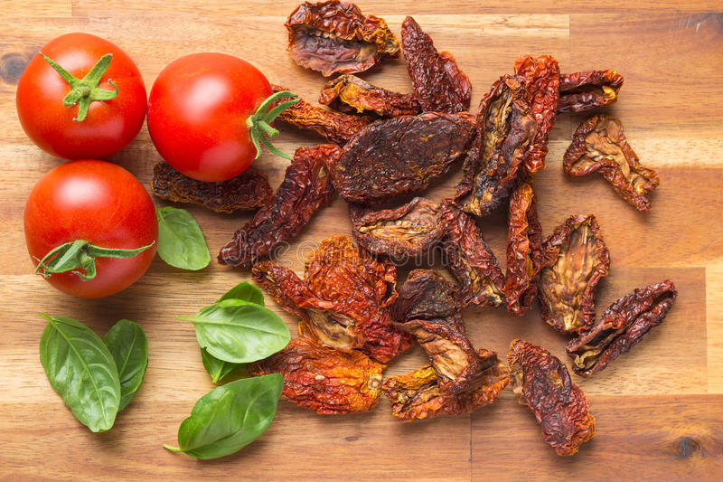 Dried sliced tomatoes and fresh tomatoes with basil leaves. stock photos