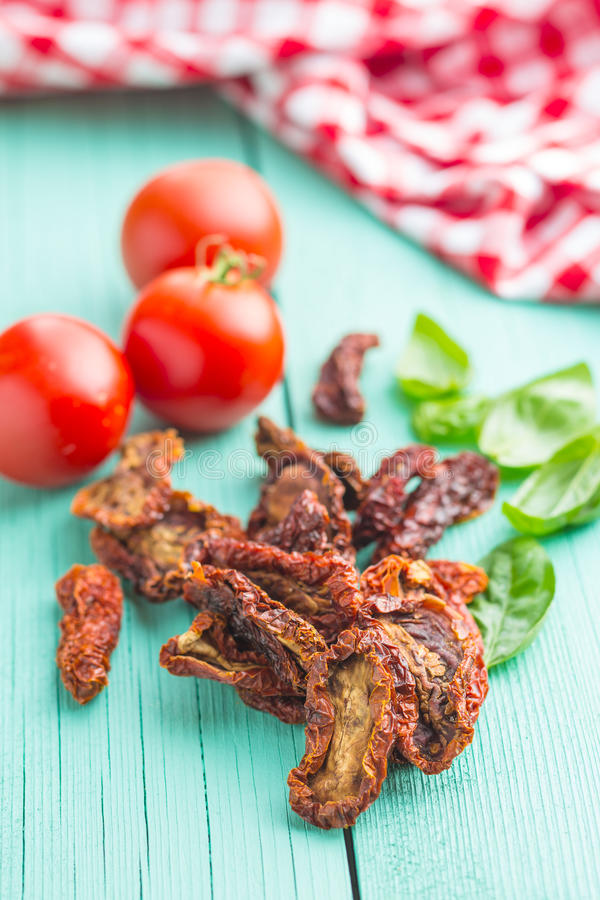 Dried sliced tomatoes and fresh tomatoes with basil leaves. stock image