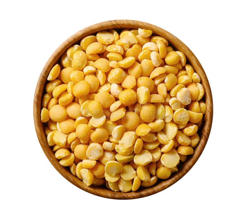 Dried splin yellow peas in wooden bowl isolated on white royalty free stock image