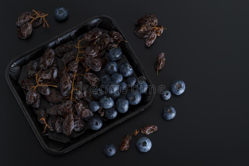 Dried sultanas and blue berries on a tray isolated on black background royalty free stock image
