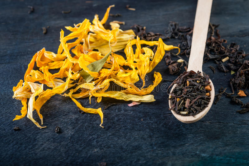 Dried sunflower petals on dark background and tea leaves. Dried sunflower petals on dark background for tea and alternative medicine royalty free stock photography