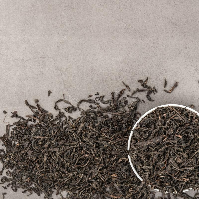 Dried tea is poured into a white ceramic cup on a gray textured background. View from above. Layout stock images