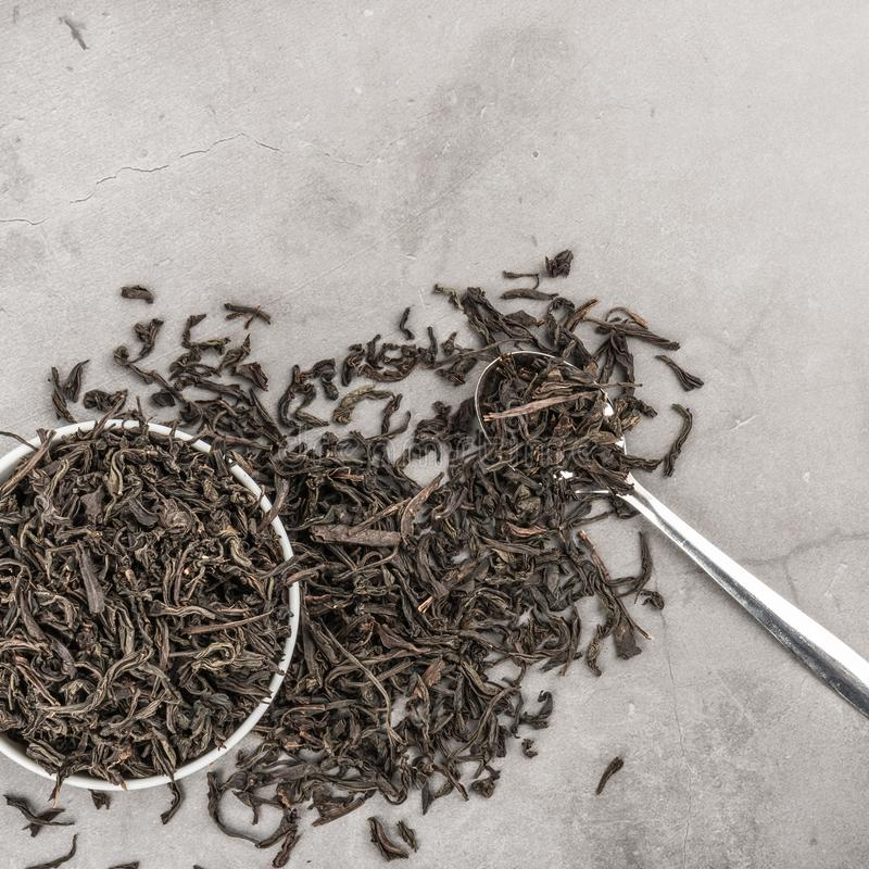 Dried tea in a white ceramic cup with a spoon on a gray textured background. View from above. Layout stock photography