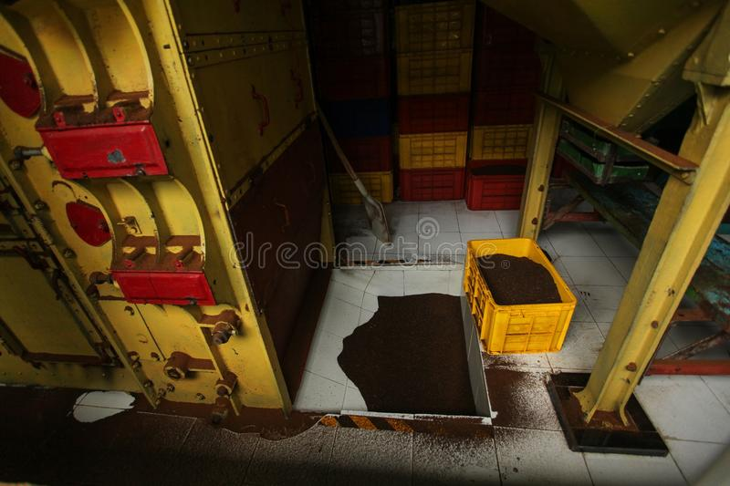 Dried tea in yellow plastic box, and some tea dust on the floor. Of tea manufacturing factory, in the dryer room. Kandy, Sri Lanka stock photography