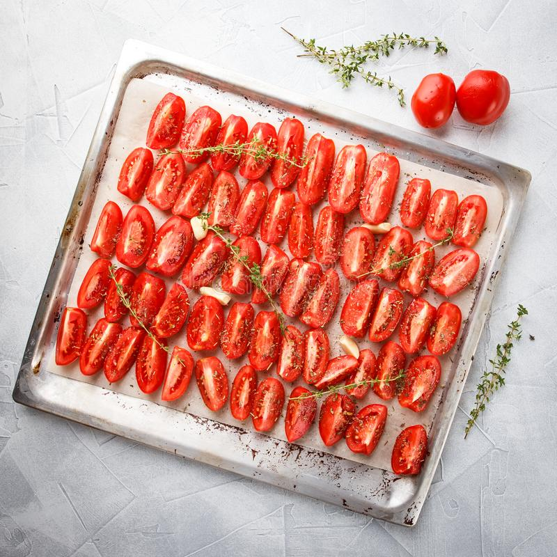 Dried tomatoes in baking tray. And spatula on blue wooden background royalty free stock photos