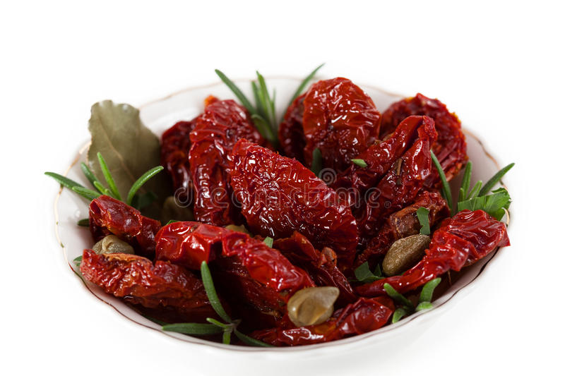 Dried tomatoes with herbs royalty free stock photos