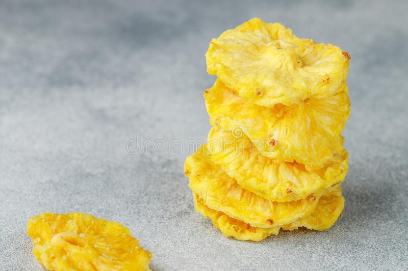 Dried yellow pineapple rings on a grey concrete or stone background. Useful Healthy snack. Selective focus, copy space stock photography