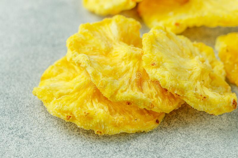Dried yellow pineapple rings on a grey concrete or stone background. Useful Healthy snack. Selective focus, copy space stock images