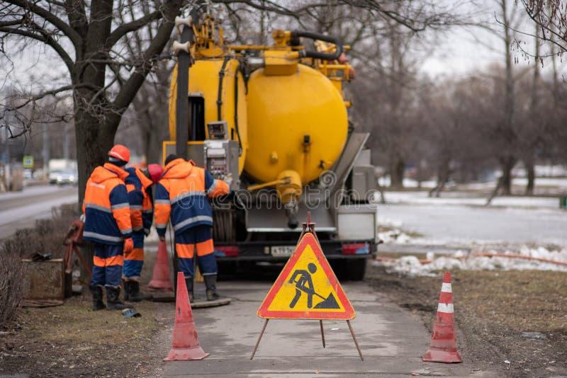 Driehoekig teken van het noodsituatiewerk aangaande de achtergrond van arbeiders en machines om water van het riool te pompen stock afbeeldingen