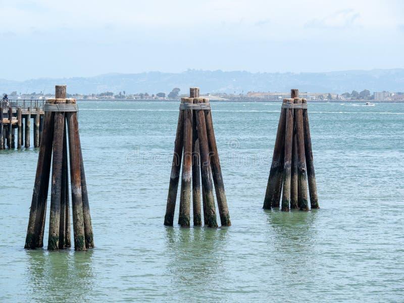 Driehoekige houten tellers die uit het water bij een dok plakken stock foto