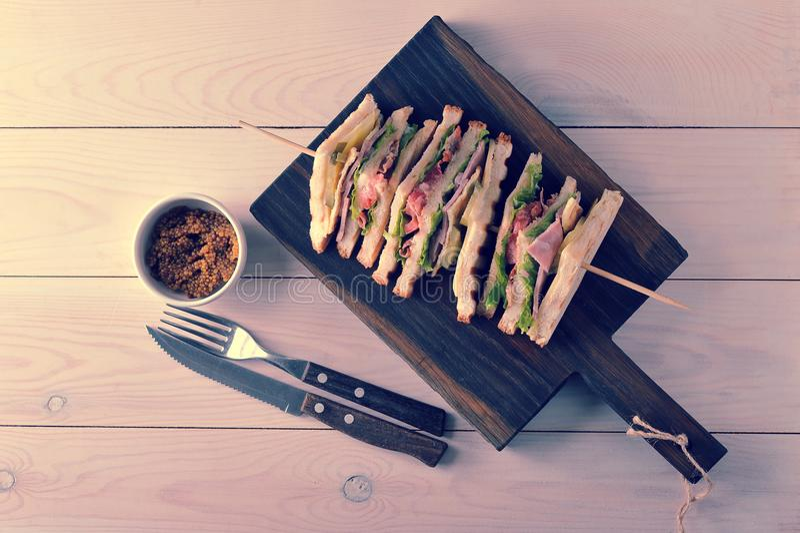Driehoekssandwiches met ham die op houten vleespennen wordt vastgebonden stock foto