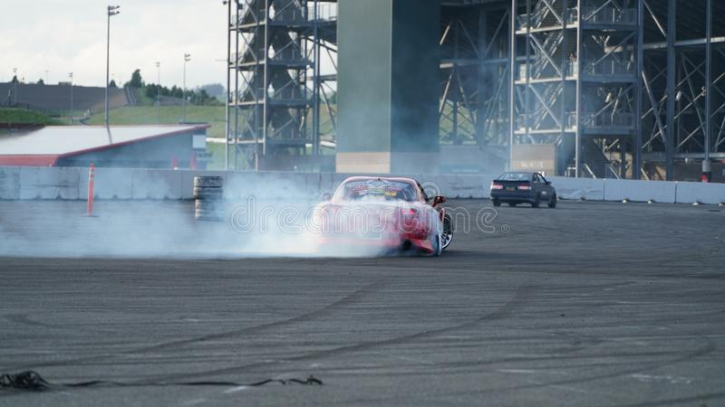 Racing car drift with smoking tyres. Drift racing, drifting car, street racing, smoking tyres and fast driving. Drift car in action stock photos